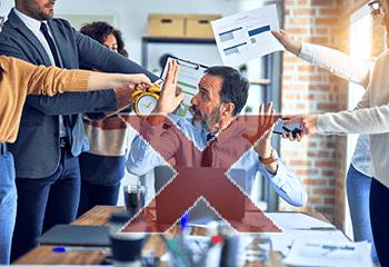 Exemple de Gestion du temps non maîtrisée : une homme à son bureau visiblement surmené et énervé avec des personnes tout autour de lui qui lui apportent encore plus de travail